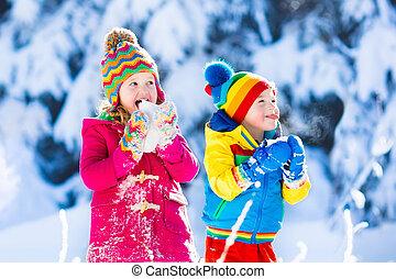 Children having fun in snowy winter park