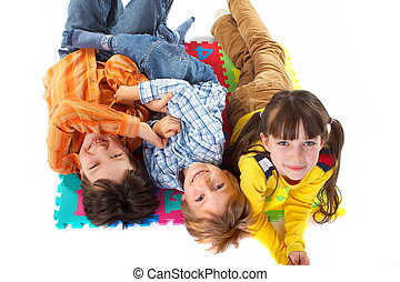 Children having fun, laying on the floor and looking up. Colorful floor mat under them.