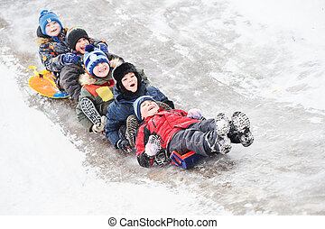 children having fun riding ice slide in snow winter