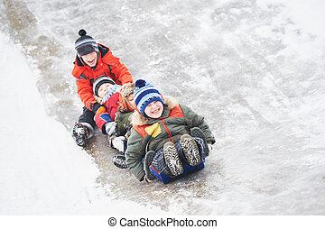 children having fun riding ice slide in winter