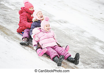 children having fun riding ice slide in winter
