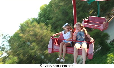 Children having fun riding in the amusement park