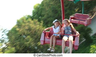 Children having fun riding in the amusement park