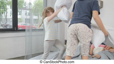 Children Having Pillows Fight On Parents Bed, Happy Family Fun In Bedroom Laughing