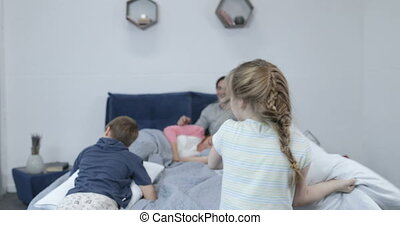 Children Having Pillows Fight On Parents Bed, Happy Family Fun In Bedroom