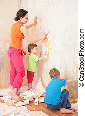 children help mother remove from wall old wallpapers