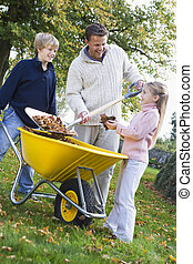 Children helping father to collect autumn leaves in ...