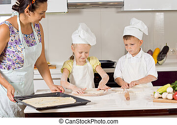 Children helping their mother to prepare the dough
