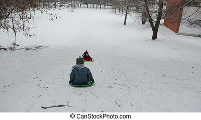 children hill winter play - two small children down a steep...