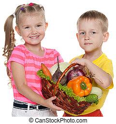Children hold a basket with vegetables