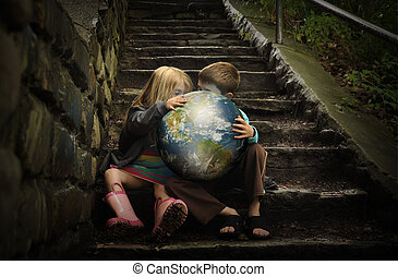 Children are holding the planet earth on wet dark stairs for a weather or season concept about the enviornment.