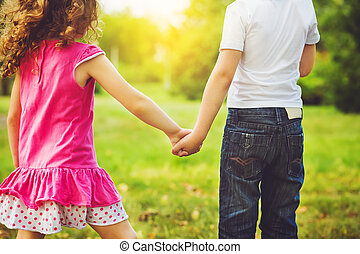 children holding his hand in summer park outdoor.