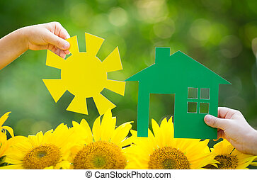 Children holding paper house and sun