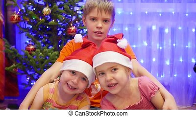 Children hugging and smiling at Christmas party. In the background, lights and garlands of Christmas fir