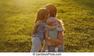 Children hugging their mother at sunset