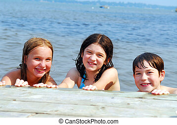 Children in a lake - Portrait of three children holding onto...