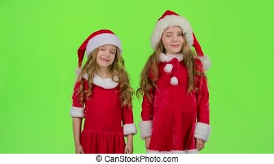 Children in a red suit are standing in the room and wink....