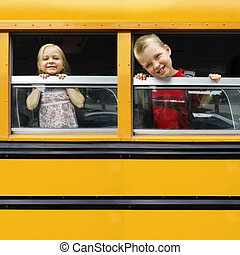 Children in a school bus - Photo of two happy children ...