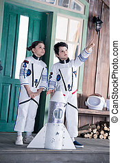 children in astronaut costumes with toy rocket pointing