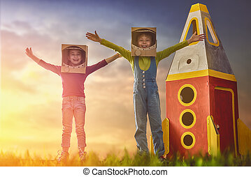 Children in astronauts costumes with toy rocket playing and...