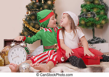 Children in Christmas costumes laughing with presents