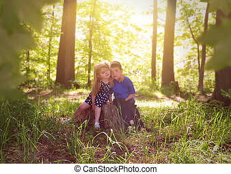 Children in Green Sunny Nature Woods - Two young children...