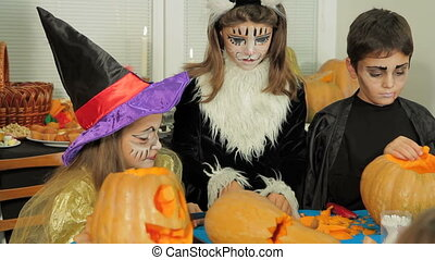 Children In Halloween Costumes Carving - Three children in a...
