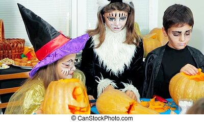 Children In Halloween Costumes Cutting Pumpkins