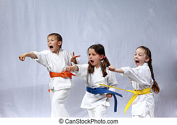 Children in karategi and with colored belts are training blows hand