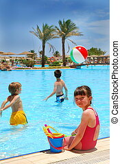 Three children playing in a pool - a little girl is sitting on the side with toys, while two boys are in the water. Beach ball is hovering over the children's heads.