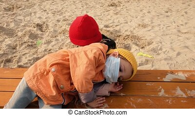Child boy and girl walking outdoors with face mask protection. Children in protective masks walk in a large sandbox and play together. Baby lay down on the bench