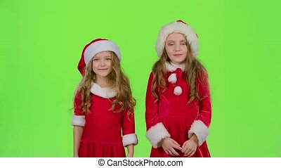 Children in red New Year hats watch a fairy tale in the...