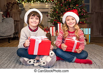 children in Santa hats with Christmas gifts