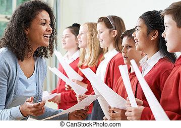 Children In School Choir Being Encouraged By Teacher