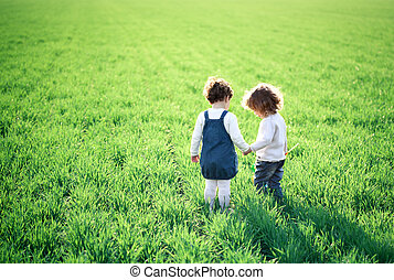 Children in spring field - Two children going in spring...