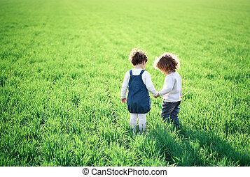 Children in spring field - Two children going in spring ...