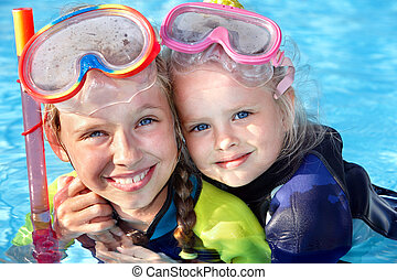 Children in swimming pool learning snorkeling.
