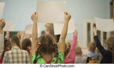 Children in the classroom are holding drawings in their hands