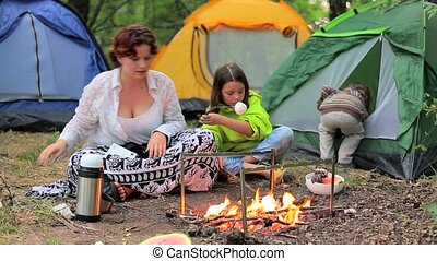 Children in the evening in the forest at the fire roasting marshmallows.