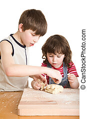 children in the kitchen making a dough