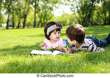 Children in the park reading a book
