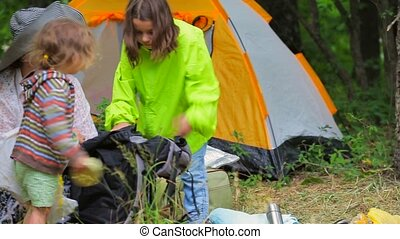 Children in the tent town sort a backpack, take out things and products.