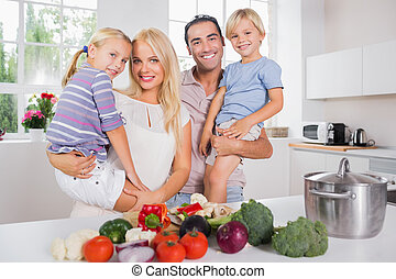 Children in their parents arms in the kitchen