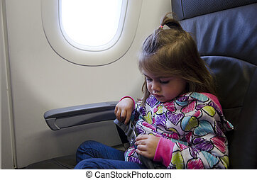 Children & Infants air travel - Young girl fast seat belt on...