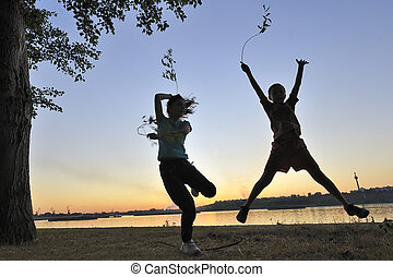 children jump against the sun