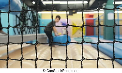 Children jump on trampolines in the children's entertainment center. Trampoline entertaining game center. Indoor. Playroom. Children have fun in the playground. 4K.