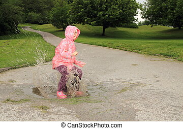 Children jumping into a puddle
