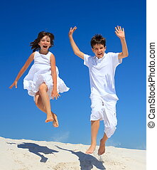 Children jumping on beach - Happy young brother and sister...