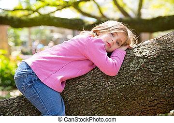 Children kid girl resting lying on a tree branch