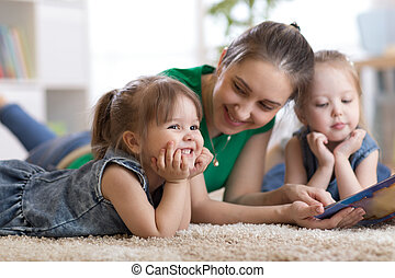 Children laughing and having fun reading stories with their mother laying on the floor at home